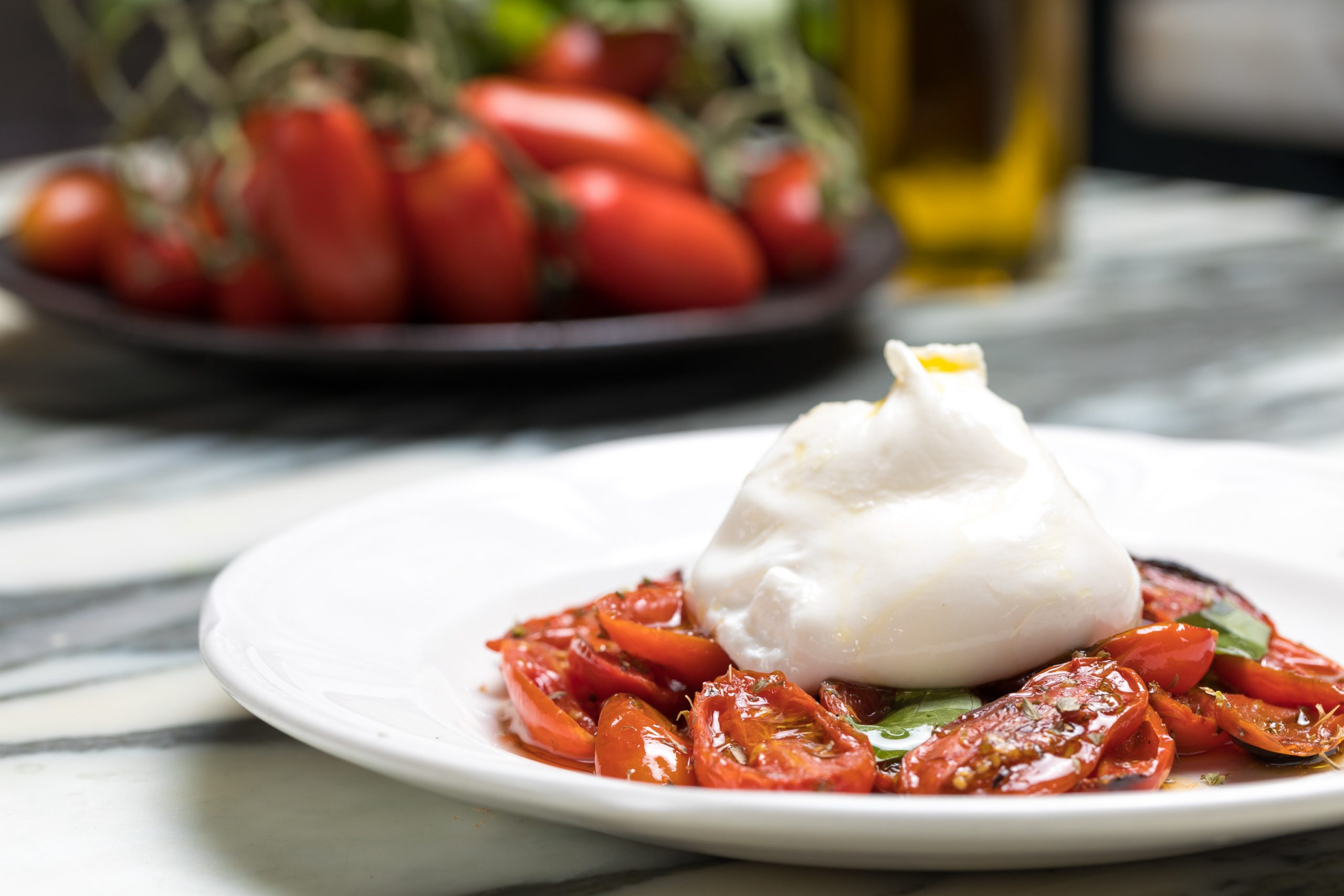 Mozzarella sitting on a bed of tomatoes - Healthy Italian Dishes